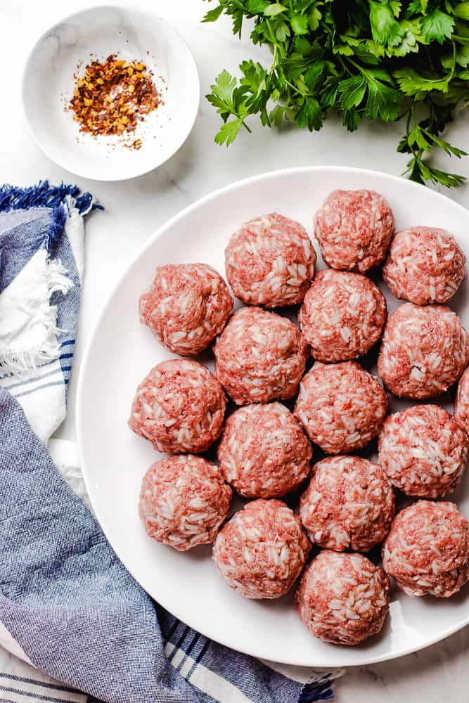 Raw meatballs on a white plate.