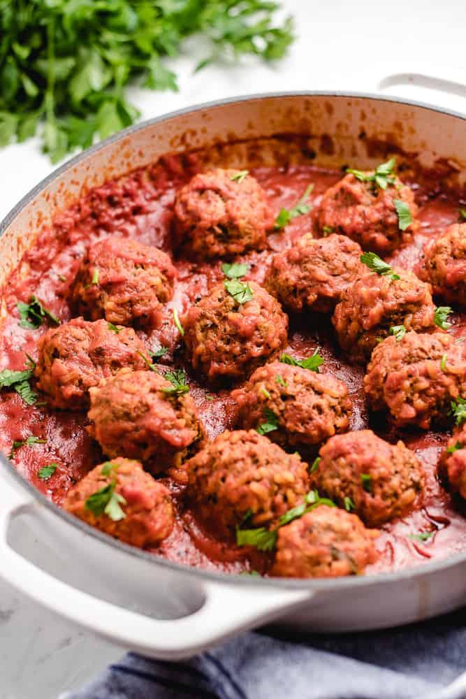 Tefteli (Russian Meatballs) in tomato sauce in white skillet.