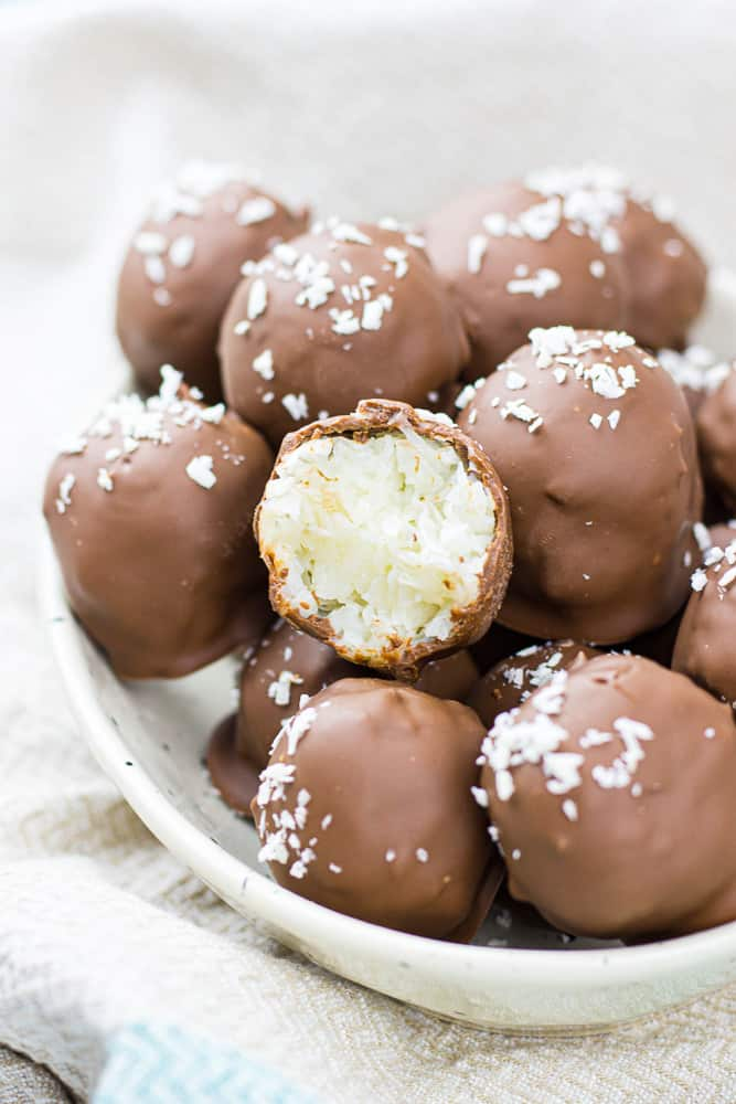 Chocolate covered coconut balls on a white plate.