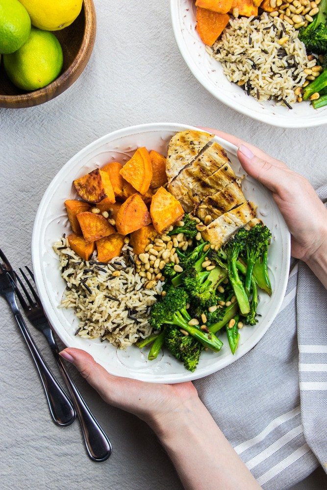Buddha Bowl with sweet potatoes, wild rice, grilled chicken and broccolini in a white bowl.