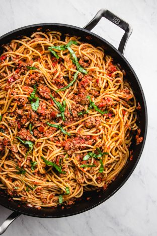 close up photo of pasta with meat sauce toppied with fresh basil.
