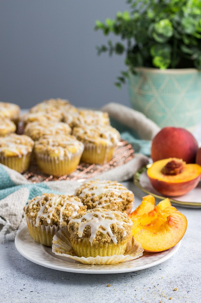 Peach Muffins topped with delicious cinnamon crumb topping and vanilla glaze is the best easy muffins recipe to celebrate summer and the early fall season!