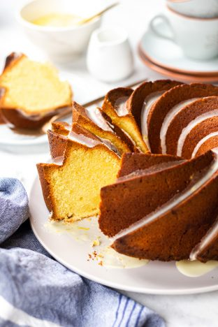Orange Pound Cake cut in slices on a light grey plate.