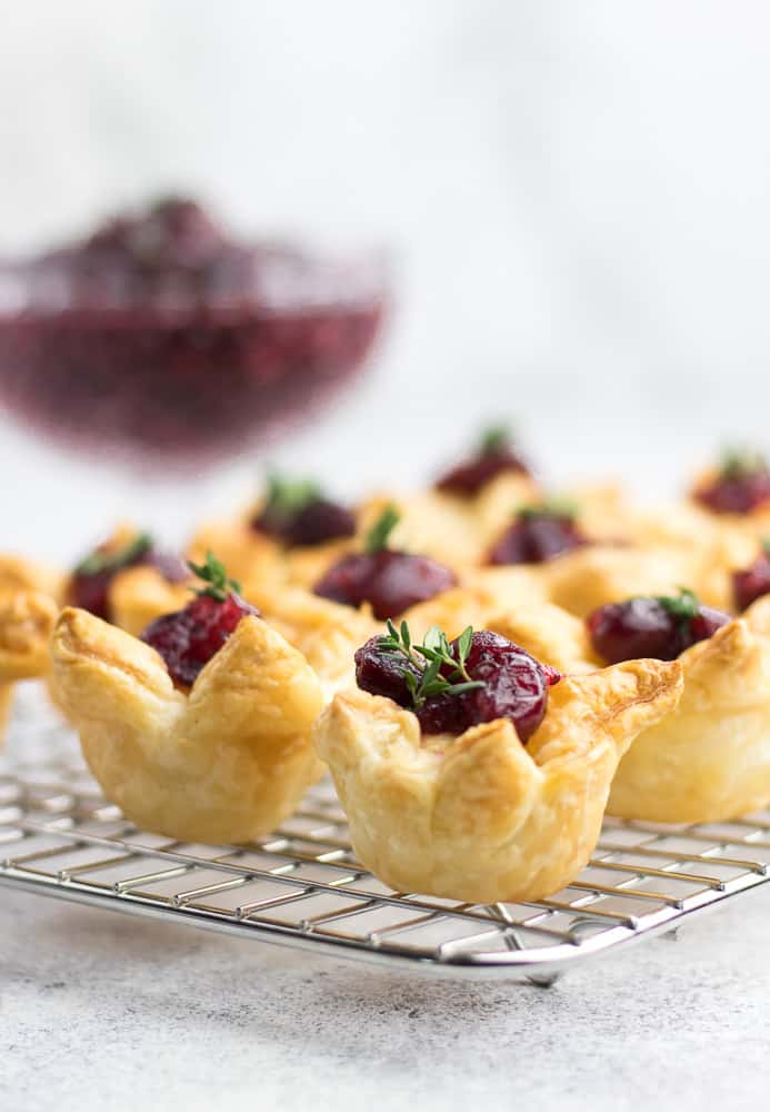 3 Ingredient Cranberry Bites is an easy appetizer for a party. Made with Puff Pastry, Brie Cheese, and Cranberry Sauce, this lovely starter will be perfect for the Holiday Season!