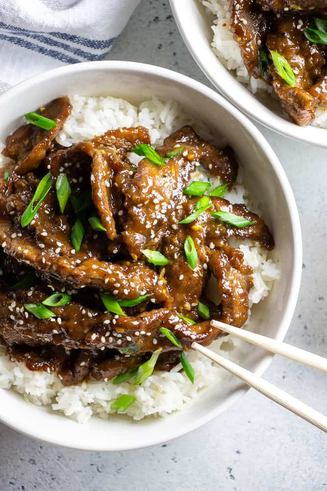 Easy Mongolian Beef recipe is a perfect quick 30 minutes dinner, made with crispy thinly sliced flank steak and coated with sweet and spicy sauce.