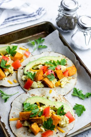 Breakfast tacos, loaded with eggs, avocado, sweet potatoes, and tomatoes, laying on a baking sheet.