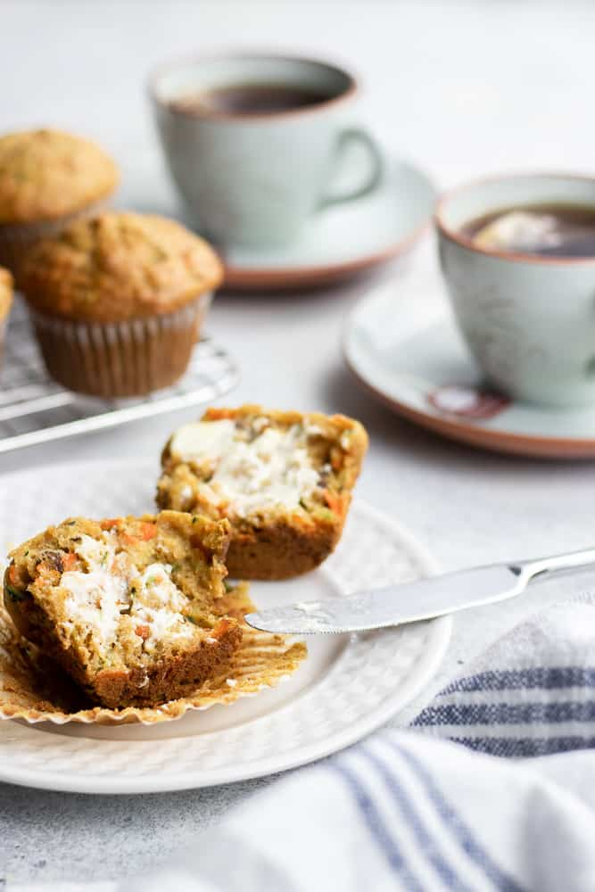 Freshly baked Carrot Zucchini Muffins with butter on a white plate next to two cups of tea.