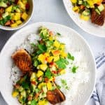 Pan seared salmon with mango avocado salsa and rice on a white plate.
