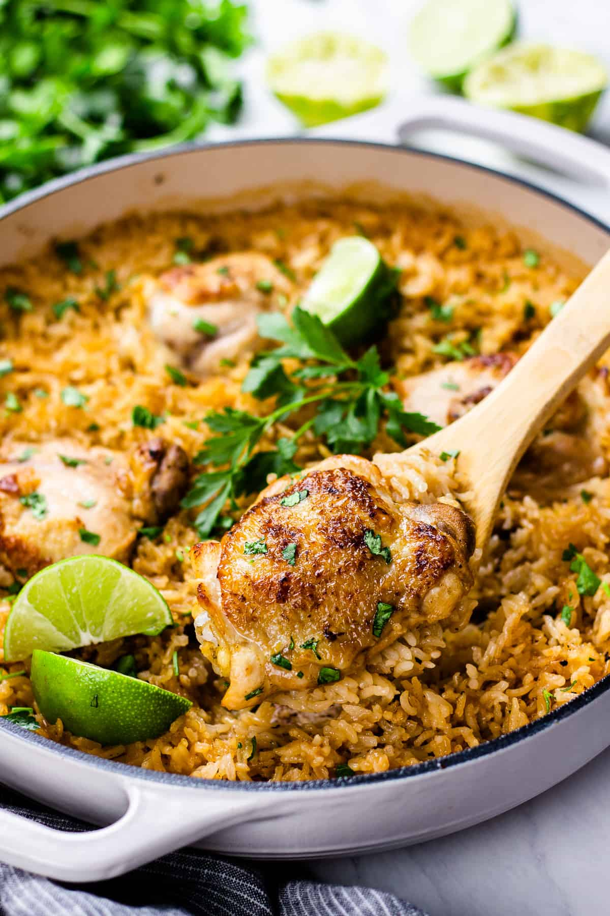 chicken with rice, cooked in white pan, and topped with parsley and lime.