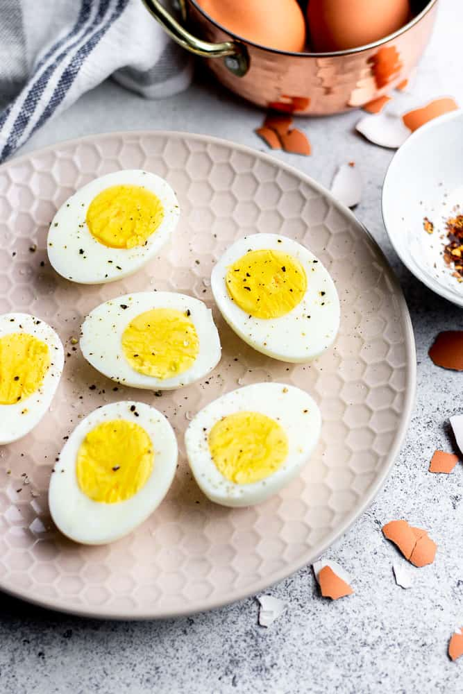 Instant Pot Hard Boiled Eggs, peeled and sliced in halves, laying on a plate.
