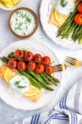 Baked Salmon topped with dill sauce, asparagus and cherry tomatoes on a vine, served on a white plate.