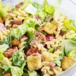 BLT Pasta Salad served in a clear mixing bowl.