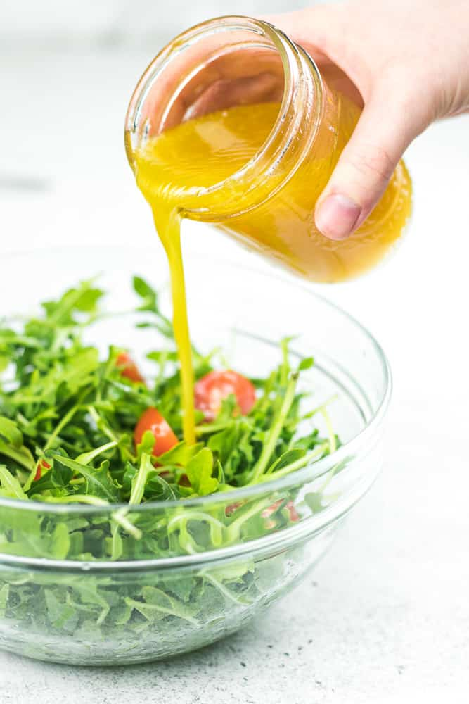 Pouring Citrus Vinaigrette into the arugula salad in a glass mixing bowl.
