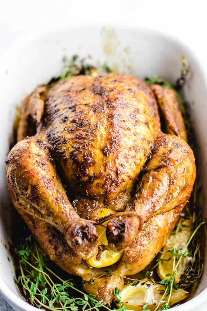 A cooked whole roasted chicken placed in a white baking pan with thyme and lemin wedges.