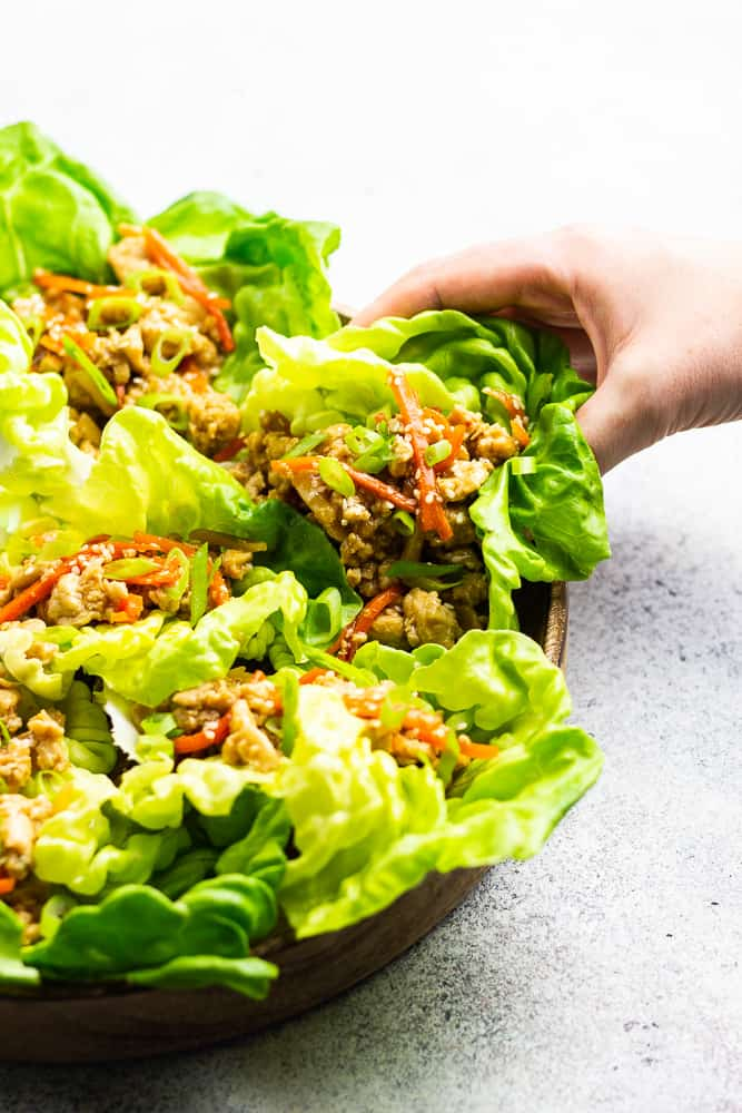 a hand is grabbing a lettuce wrap from a wooden plate.