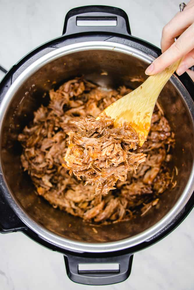 Pulled pork with a wooden spoon in instant pot.