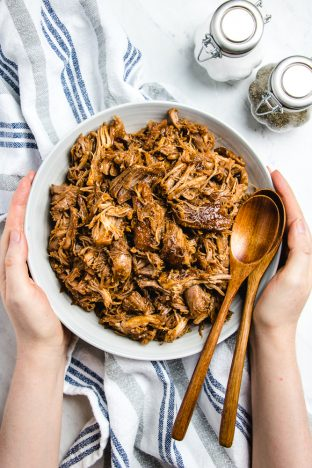 Two hands hold a bowl with pulled pork and two woden spoons on a white table.