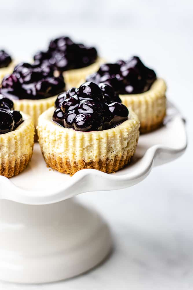 mini cheesecakes with blueberry sauce on a white cake plate.