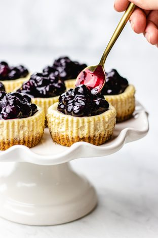 seven mini cheesecakes with blueberry sauce on a white cake plate.