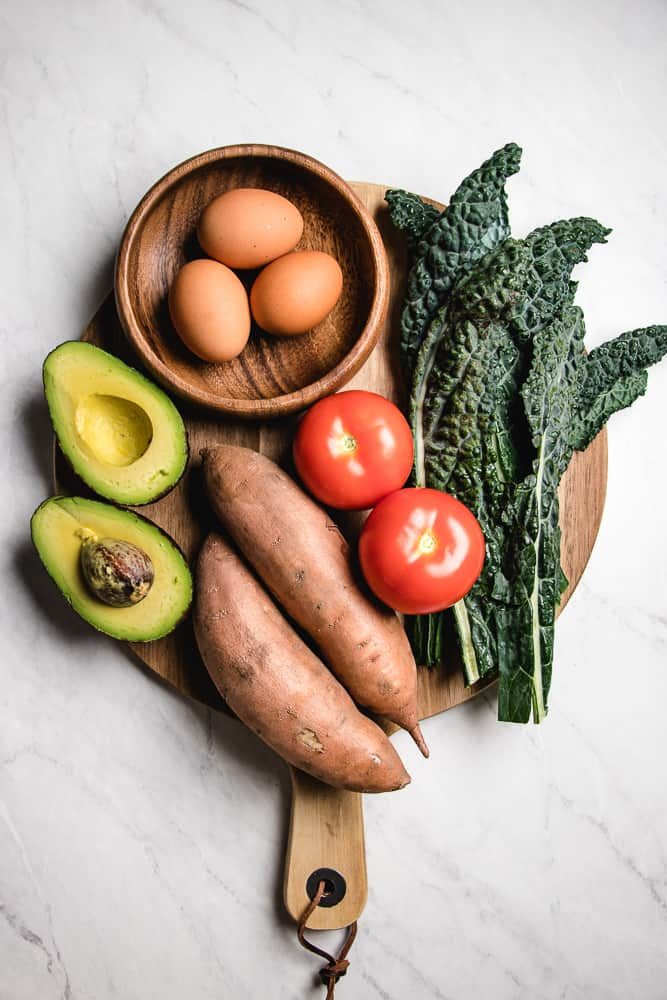 avocado, eggs, kale, tomatoes, and sweet potatoes on a wooden board.