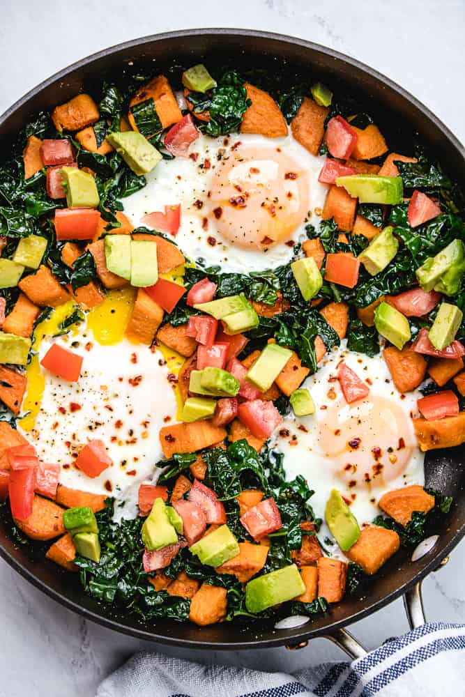 Breakfast hash in a skillet with eggs, sweet potoatoes, kale, tomatoes, and avocado.