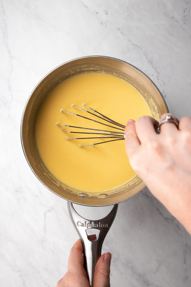 whisking cheese sauce in a sauce pan