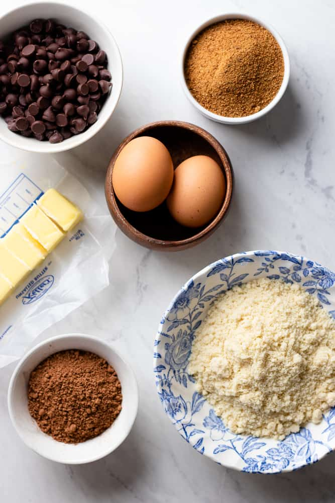 ingredients for brownies: chocolate chips, butter, eggs, coconut sugar, almond vlour, and cocoa powder