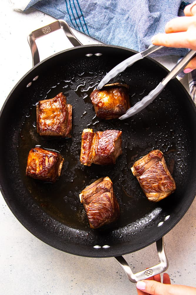 Seared bone-ib short ribs in a skillet.