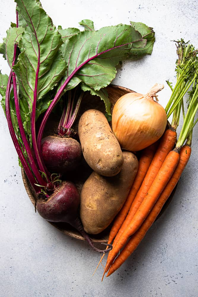 Beets, potatoes, onion, and carrots on a wooden plate.