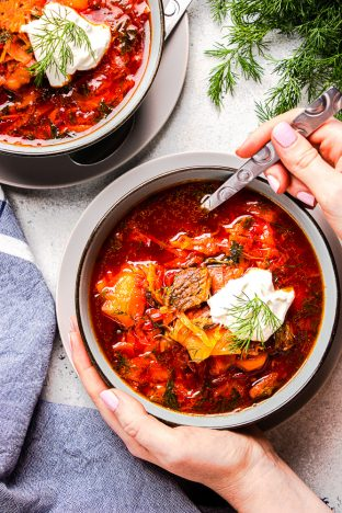 Borscht soup topped with sour cream in a bowl