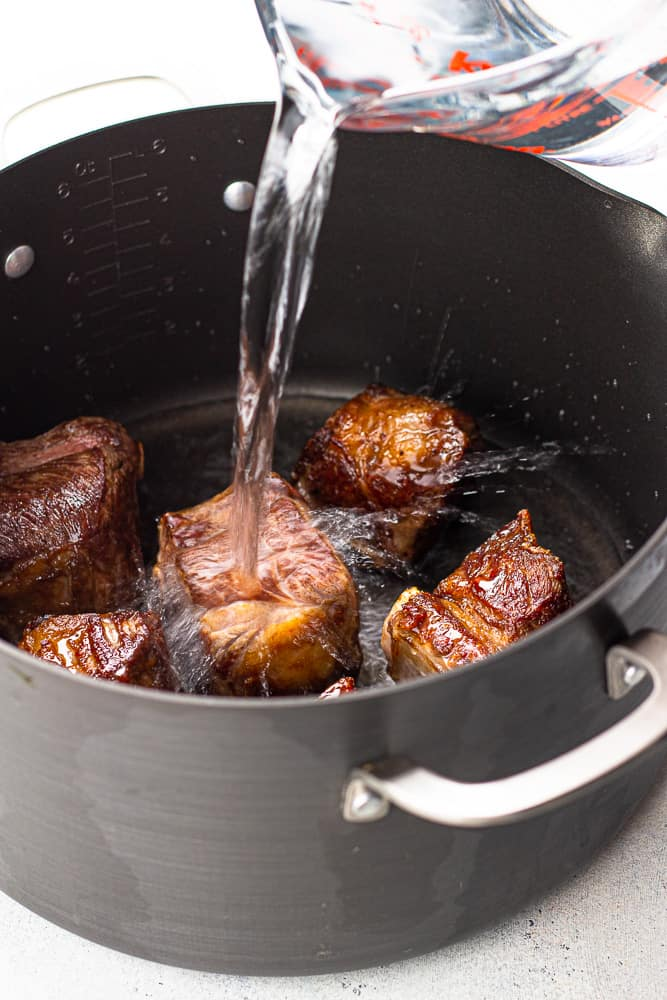 Pouring water in a pot with bone-in short ribs for bone broth.