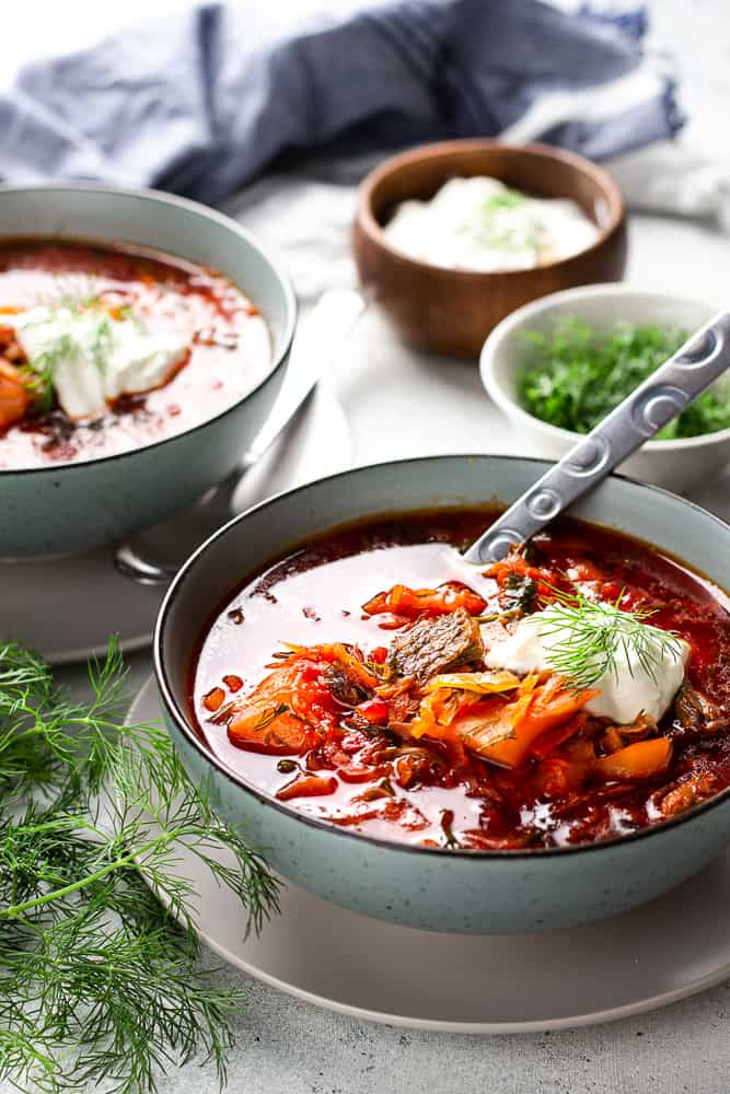 Borscht soup topped with sour cream in a bowl.