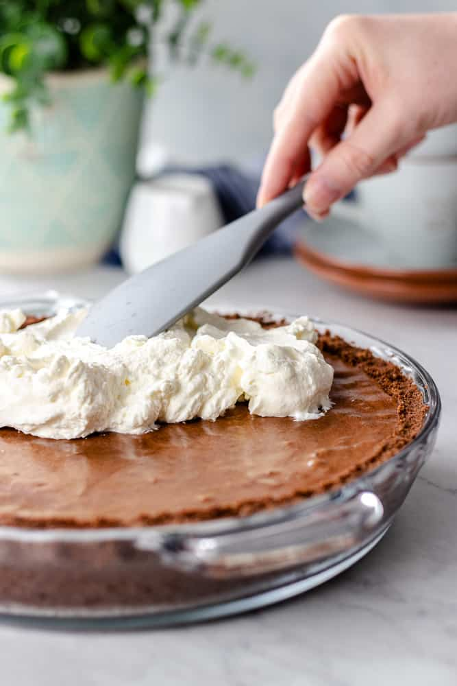 topping chocolate mousse pie with whipped cream.