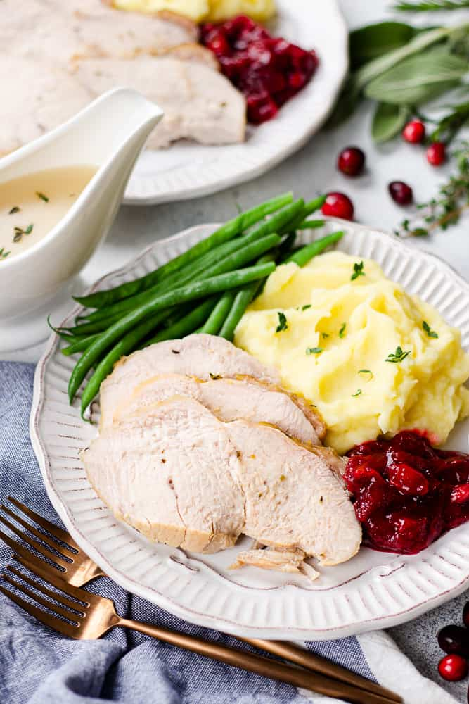 Oven Roasted Turkey Breast, mashed potaotes, green beans, and cranberry sauce on a white plate.