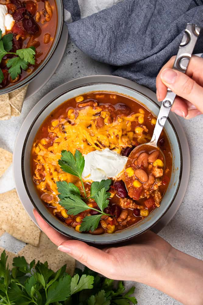Instant Pot Turkey Chili topped with cheddar cheese, sour cream, and cilantro.