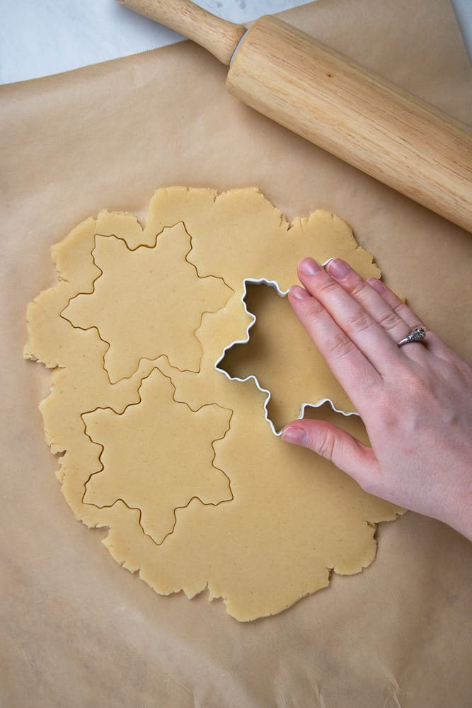 Cutting out sugar cookies with snowflake shaped cookie cutter.