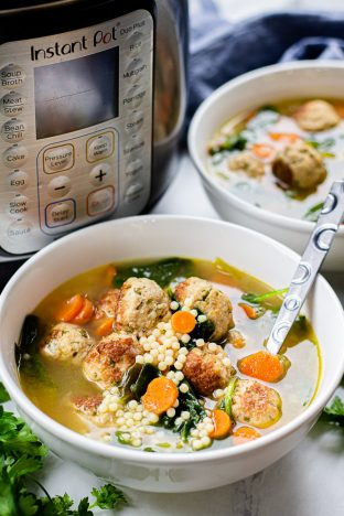 Italian Wedding Soup with turkey meatballs, acini de pepe pasta, and spinach in a white bowl.