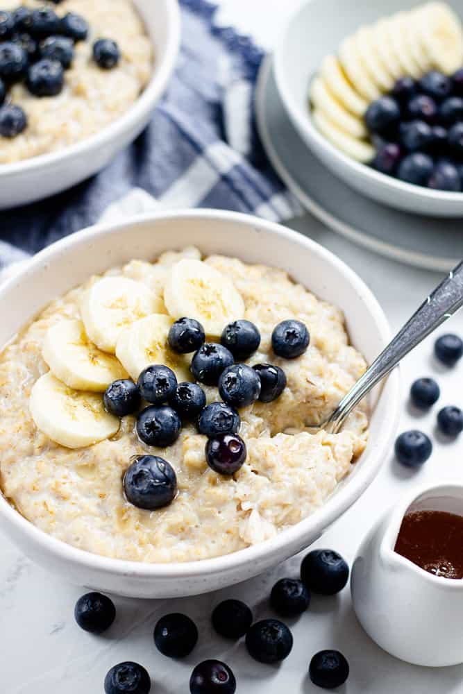 oatmeal, topped with bananas and blueberries, in a white bowl.