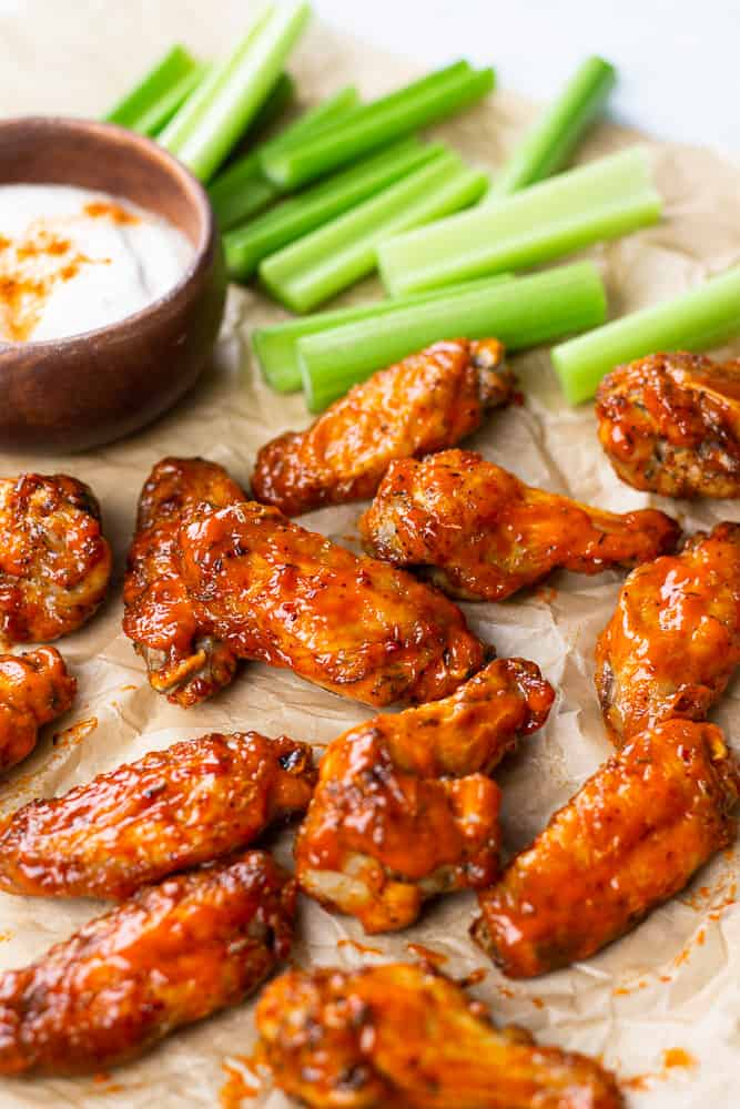 Oven Baked Buffalo Wings with ranch dressing and celery sticks on parchment paper.