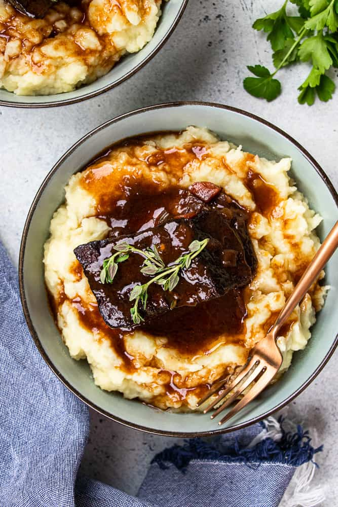 Red Wine Braised Short Ribs on top of mashed potatoes, served in a blue bowl.
