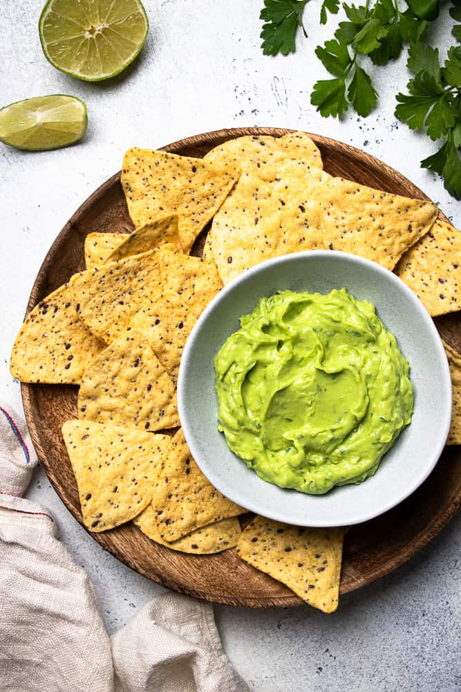 Avocado dip in a bowl with tortilla chips around.