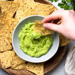 Scooping avocado dip with tortilla chip.