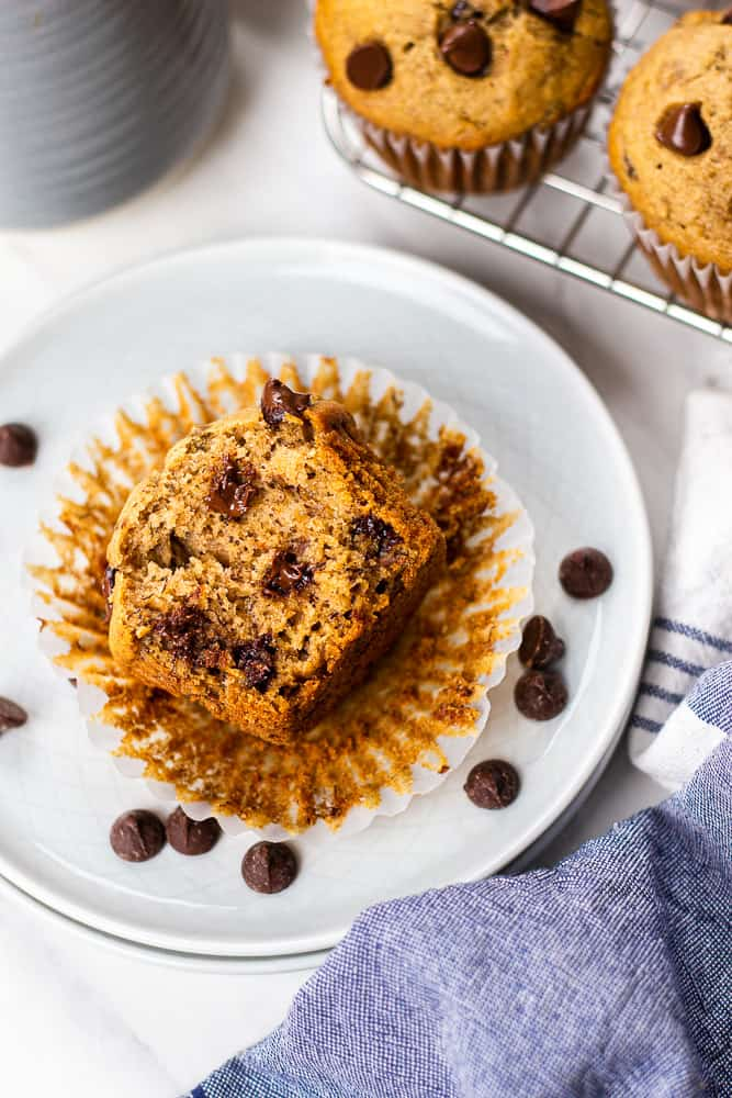 A bite shot of Healthy Banana Chocolate Chip Muffins on a small white plate.