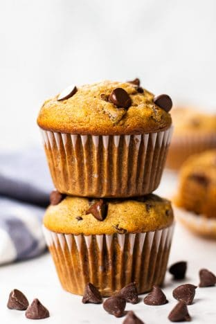 Two banana chocolate chip muffins on top of each other.
