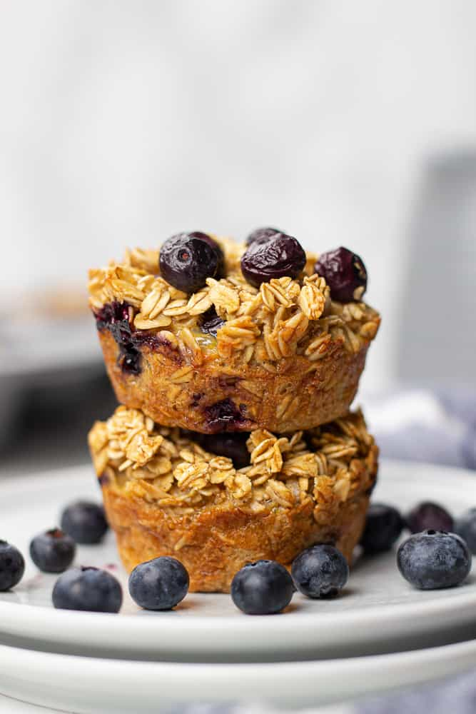 Two Blueberry Baked Oatmeal Cups on a plate with fresh blueberries.