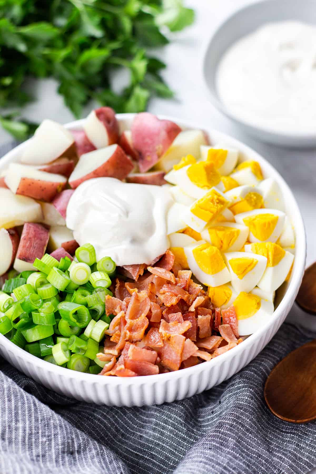 diced Red potatoes, eggs, bacon, green onion, and dressing in a white bowl.