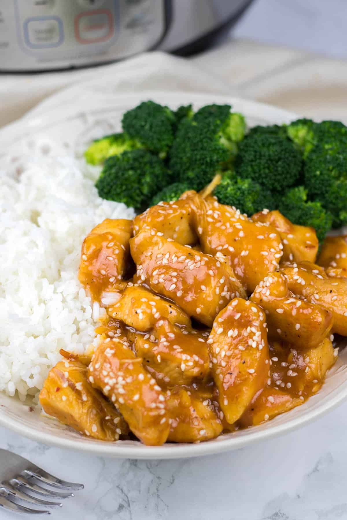 Orange Chicken served with rice and broccoli on a white plate.