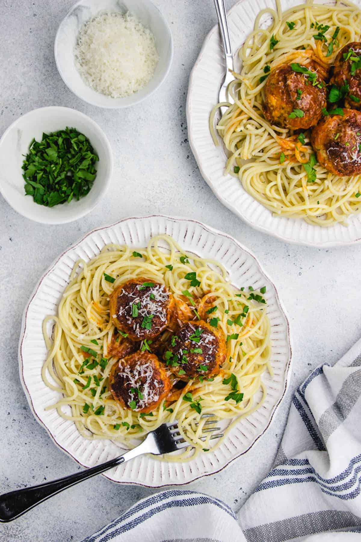 Turkey meatballs, served with spaghetti on a white plate.