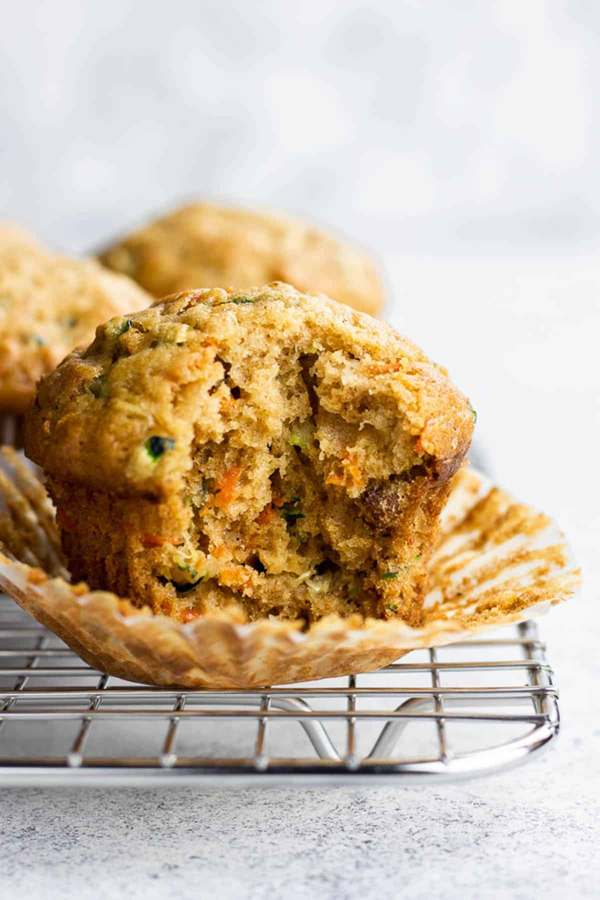 A bite shot of carrot zucchini muffin on a wire rack.