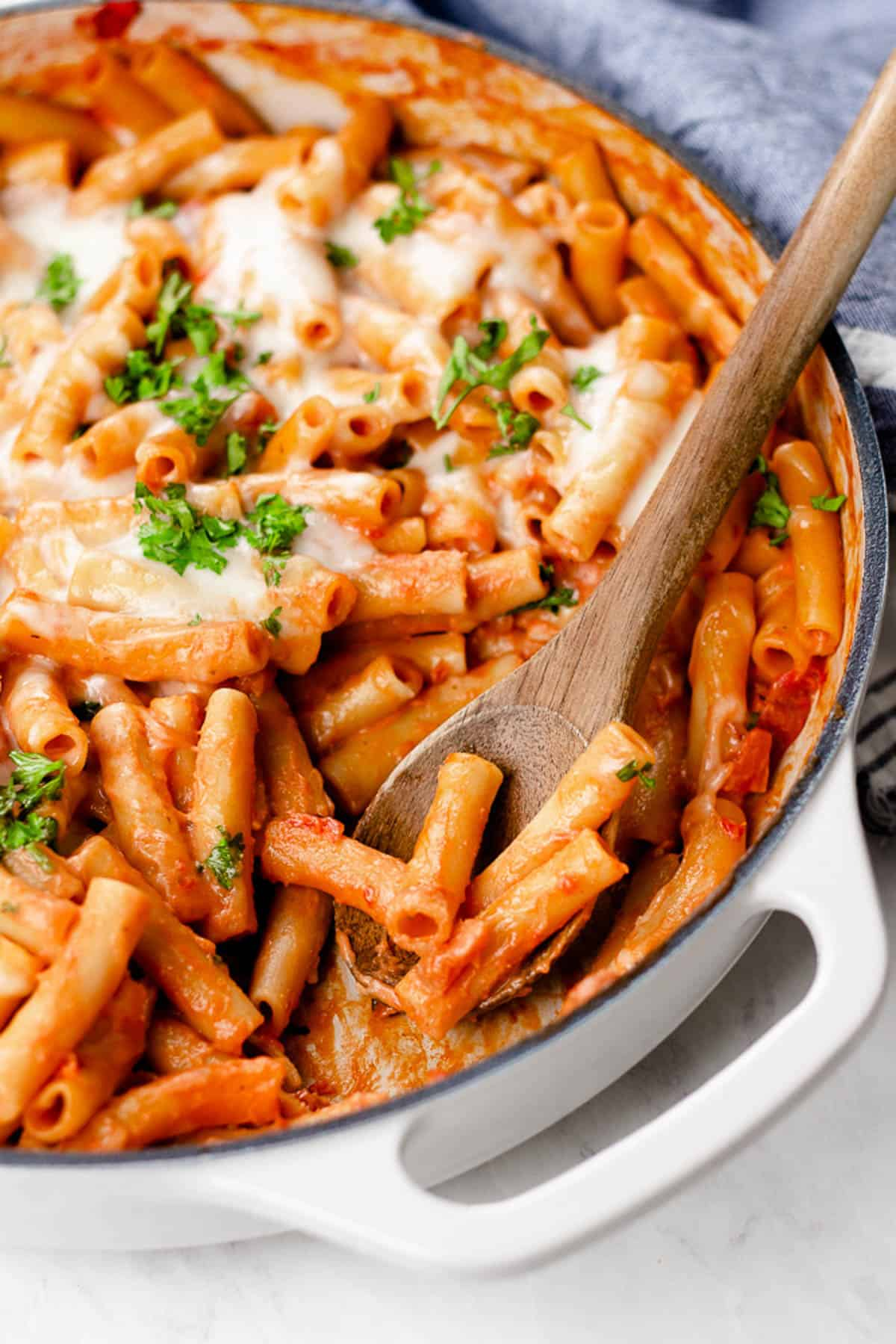 Cheesy baked ziti in a white casserole pan.